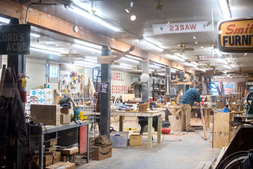 Interior of the workshop at Scotsman General Store. There are signs and tools and workbenches and a man is working in the background.