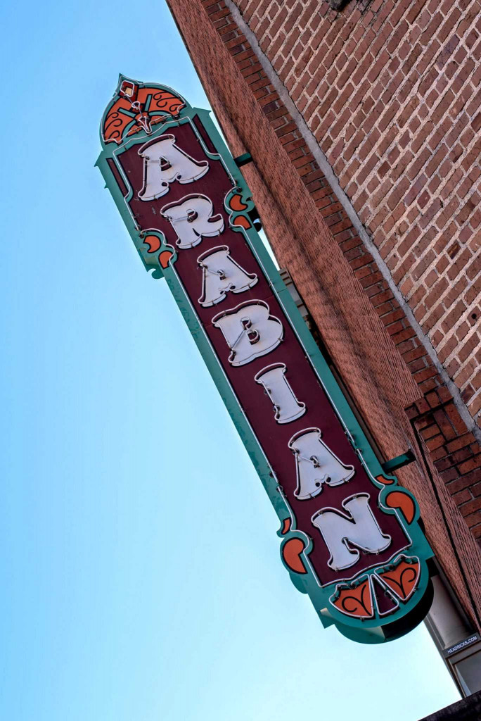 Sign from the old Arabian movie house silhouetted against a blue sky. The little theater. Plays are held in the old Arabian movie house.