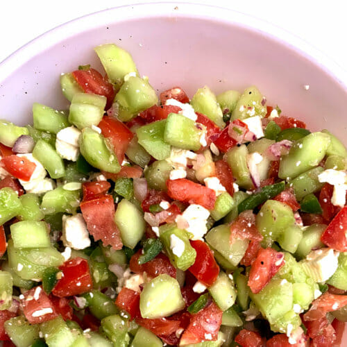 pale pink bowl of chopped cucumber salad with tomatoes, green pepper, and feta cheese
