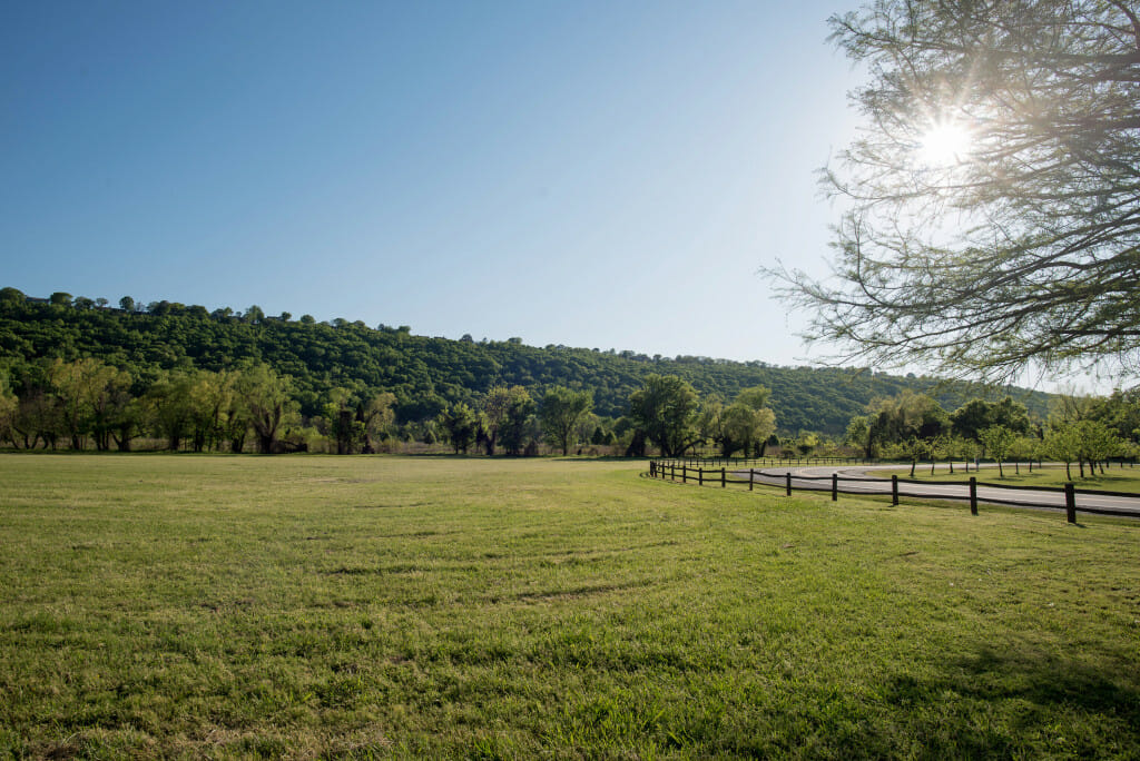 large expanse of green field with a wooded hill rising in the background and a blue sky. There is a wooden rail fence on the right side. This is Two Rivers Park a gorgeous park in Little Rock, Arkansas perfect for Biking, walking, and jogging.