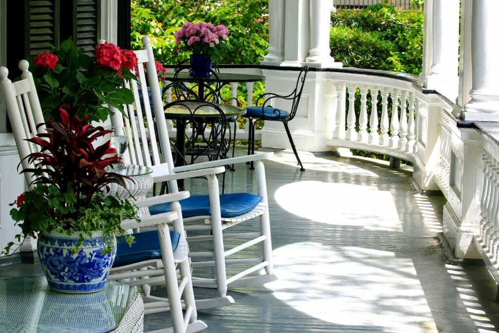 A front porch with a curved railing and columns. The porch floor is painted grey. There are white rocking chairs with blue cushions. In the distance you see a table and chairs. There are pretty flowers on the porch.  Some ideas for how to decorate a southern porch.
