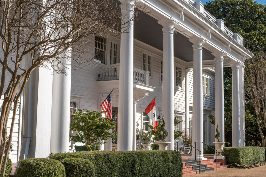 Majestic front porch of the Fairview Inn in Jackson Mississippi. The porch has large white columns in a traditional southern style. There are white rocking chairs on the porch. The porch ceiling is painted grey. The house itself is white. This photo can give you some ideas for how to decorate a southern porch. There are topiaries and plants and the US Flag as well as the state flag of Mississippi. Porch decor ideas.