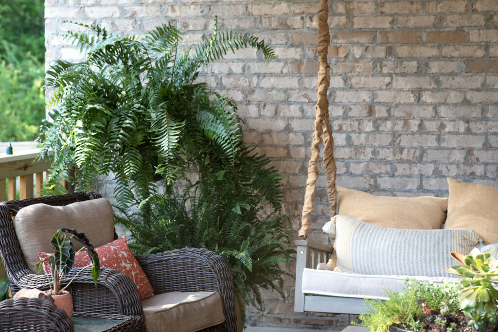 photo of a covered porch. There is a wicker chair with cushions and a hanging swing with cushions. The chain of the swing is covered with burlap. There are ferns in the corner. How to decorate a southern porch.
