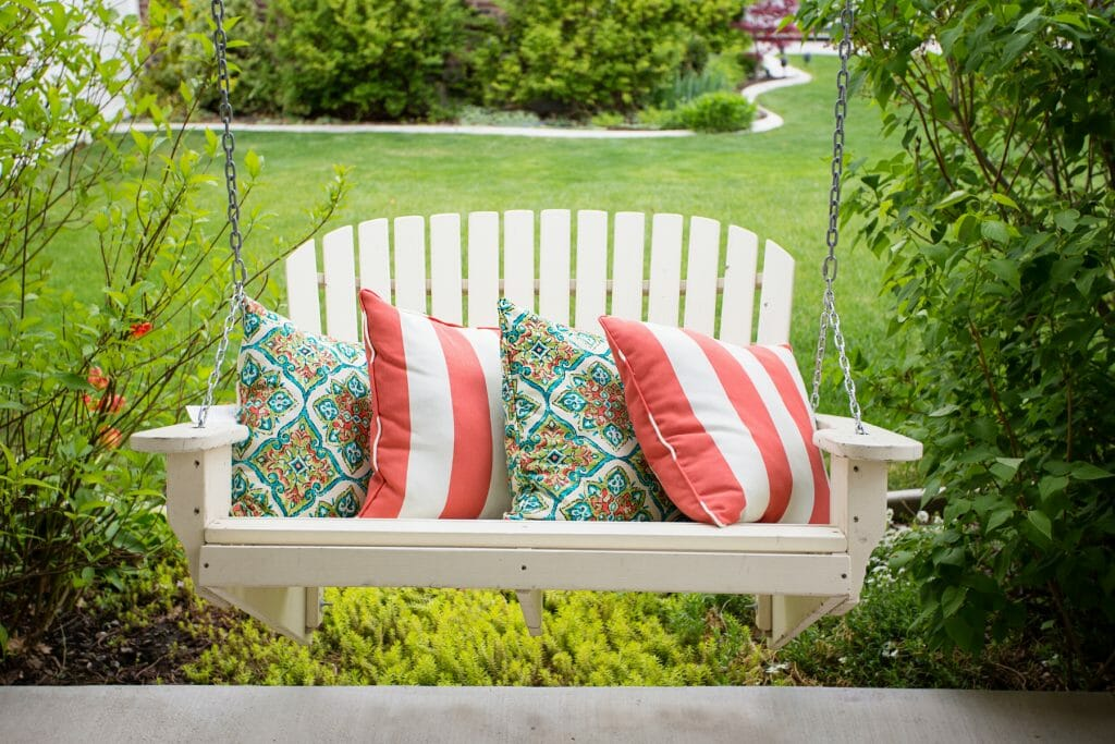 white porch swing with cushions on it. Porch decor ideas. Soften it up with lots of cushions!