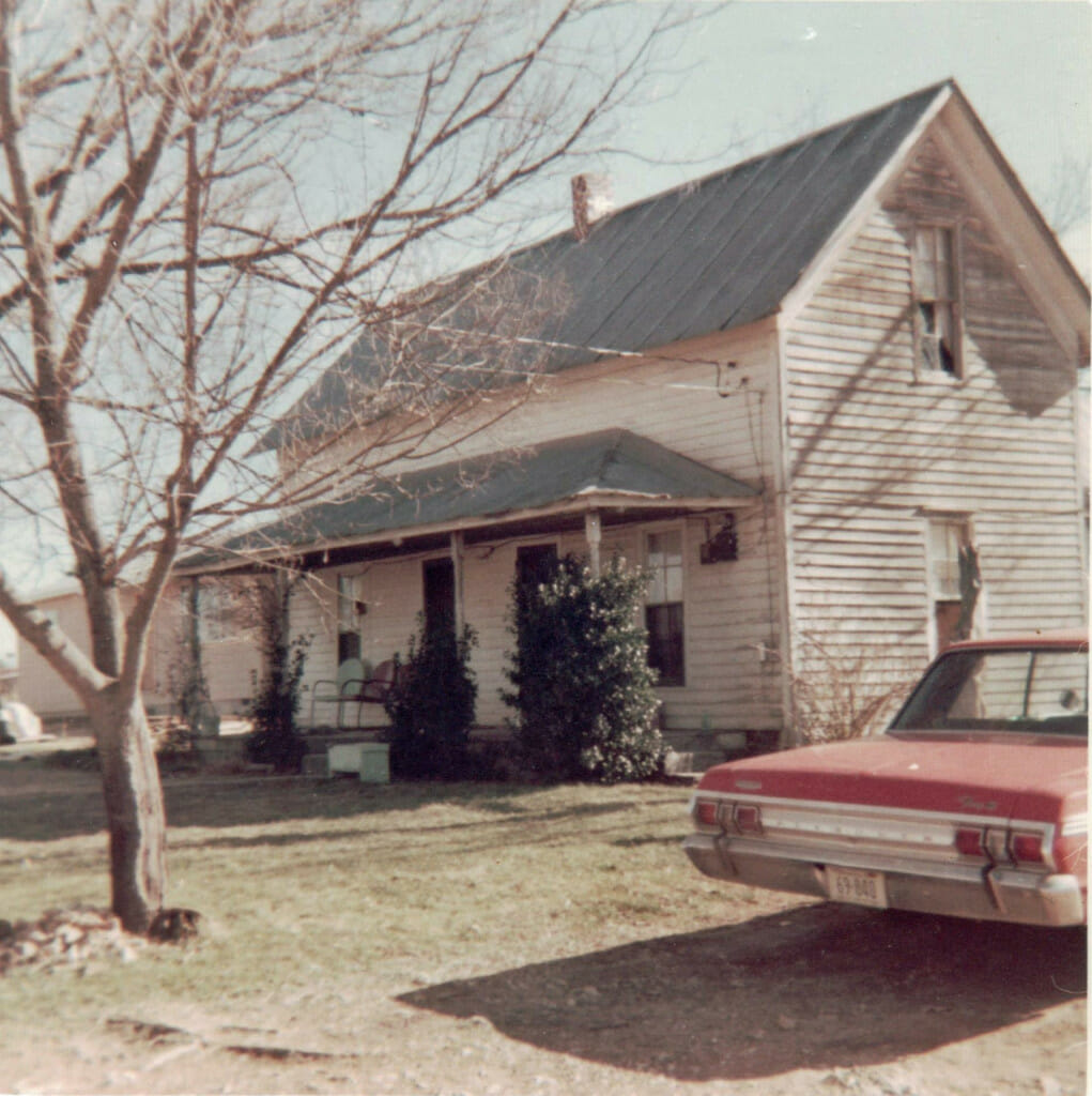 Old country house with a southern front porch. The photo is obviously from years gone by. The roof is a grey tin. The paint on the house is white, but is peeling and faded. There are two metal chairs on the front porch and a retro car in the foreground. The picture itself is faded.