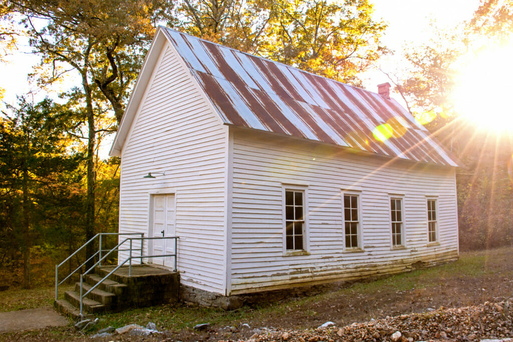 The old Erbie church in Arkansas. Sun is shining brightly at the back of the church.