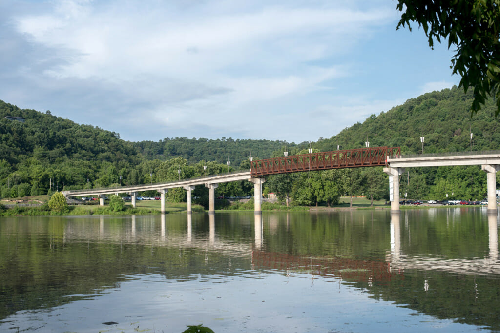 View of the pedestrian bridge at Two Rivers Park that crosses the Little Maumelle River. The view is in summer and the hillsides are wooded and the sky is blue.