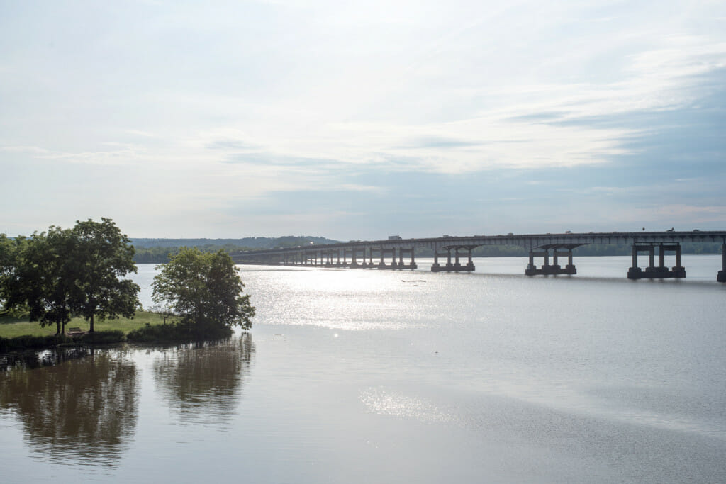 View from the pedestrian bridge at Two Rivers Park. You can see the tip of the park on the left side with a park bench and Interstate 430 stretches out across the Arkansas River. It is early morning and the sun is glistening on the water of the Arkansas River.