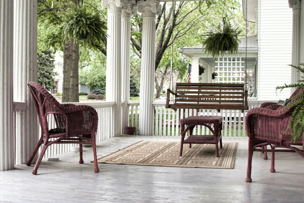 A formal porch with gorgeous columns and a floor that is painted gray. There is a brown porch swing and some wicker chairs that are painted an egg plant color. Ideas for summer porch decor.