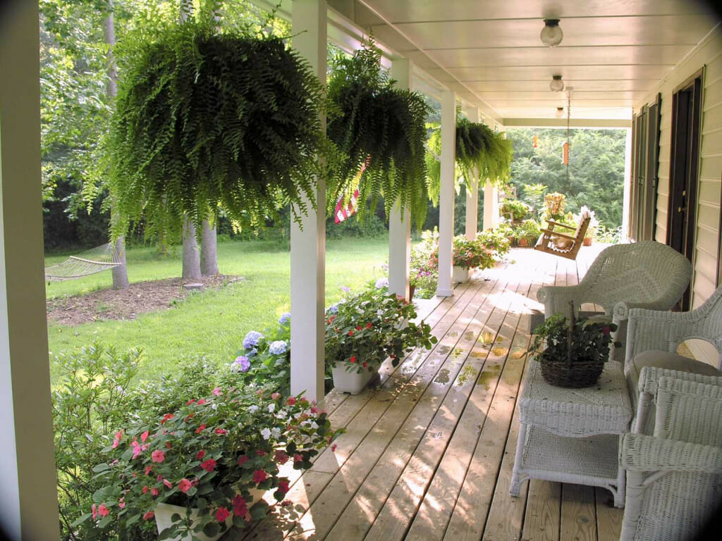 This is a porch with white wicker chairs and a white wicker table. There are ferns hanging from the porch and lots of pots of flowers. You can see a porch swing in the distance. porch decor ideas.