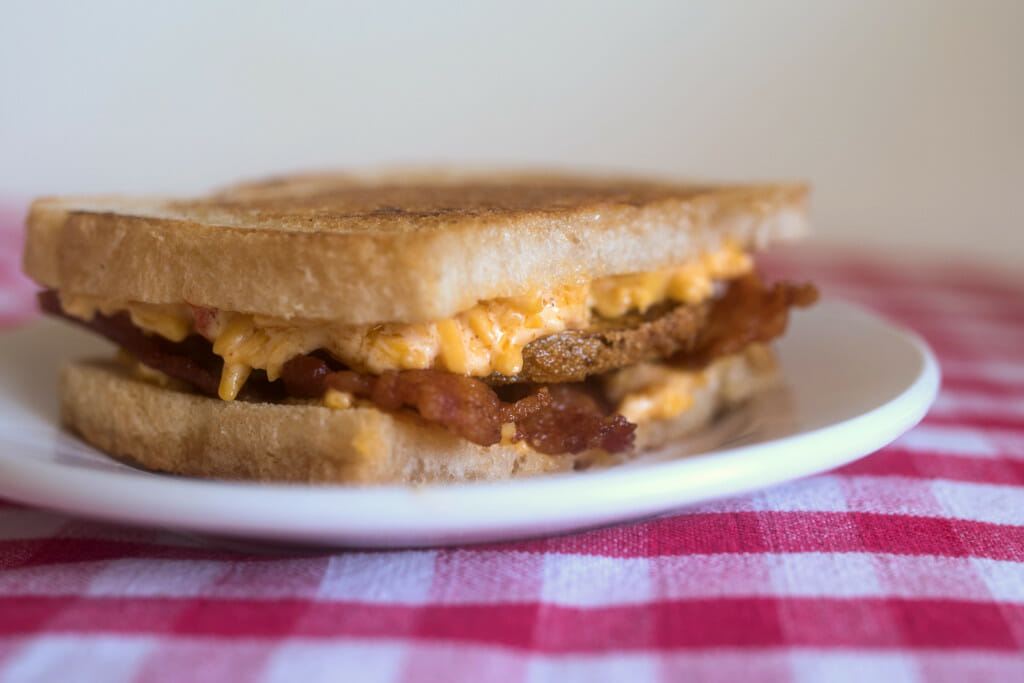 Grilled pimento cheese sandwich with bacon and fried green tomatoes on a white plate on a red gingham tablecloth.