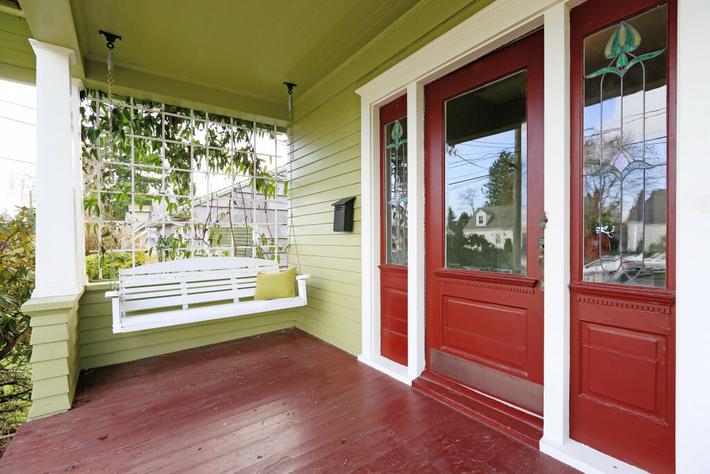 This is a white porch swing hanging on the front porch of a green house. The doors and wooden porch floor are painted a deep red. This is part of a post about southern porch decor ideas.