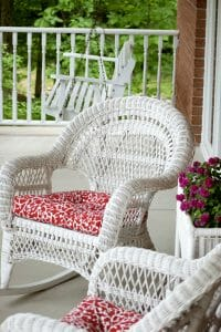 You see two white wicker chairs on a porch with red and white cushions. A wicker plant holder is between the chairs and you can see a porch swing in the background. Ideas for porch decor.