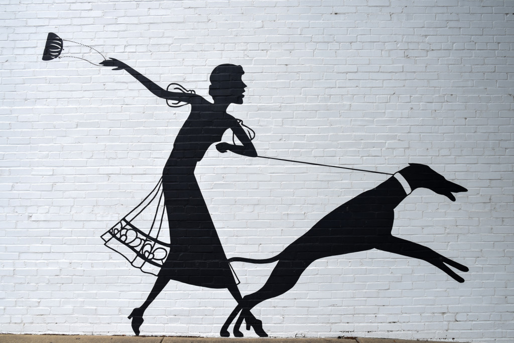 Silhouette of woman with dog is a mural on the wall of the Esse Purse Museum. One of the street murals in Little Rock, Arkansas
