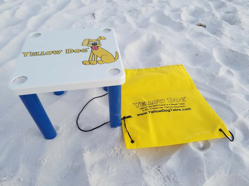 picture of a table on the beach in the sand. Yellow Dog tables are a great gift idea. These are made in Florida.
