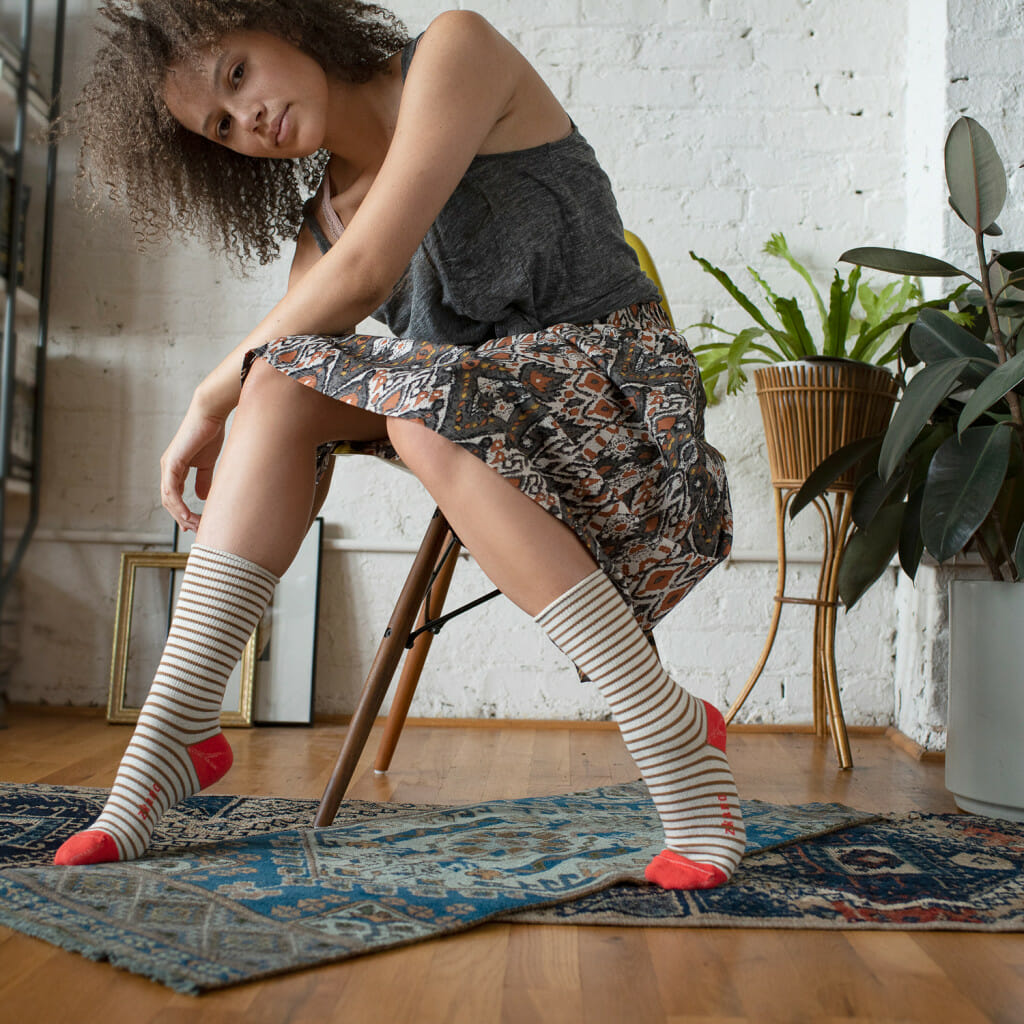 Photo of a woman in a chair with socks on. These are Zkano socks. All made in Alabama and all made from organic cotton. Zkano socks would be a wonderful southern gift to give to your loved ones.