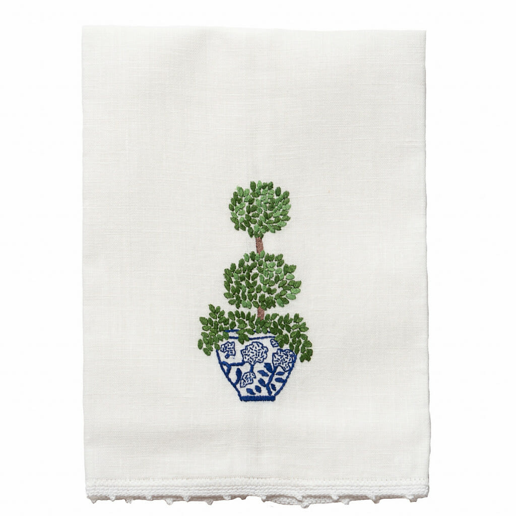 A photo of a hand towel that is embroidered. This hand towel is from Hibiscus Linens. It is white and embroidered with a vase with a topiary. Hibiscus linens are made in the south and would be a perfect southern gift.