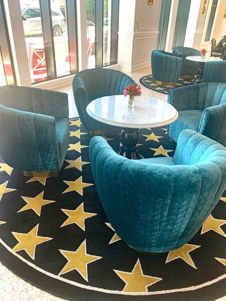 teal chairs on a rug patterened with stars at the Graduate hotel in nashville.