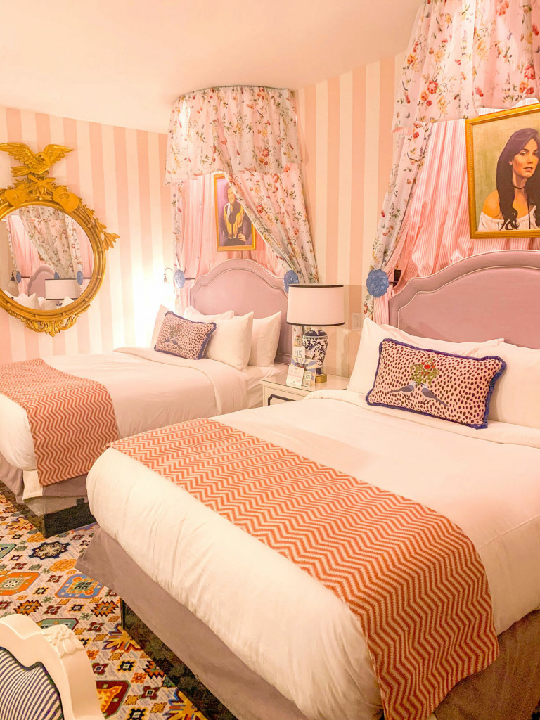 hotel room with pink headboards, patterned rug, and pink and white striped walls in Graduate hotel Nashville.