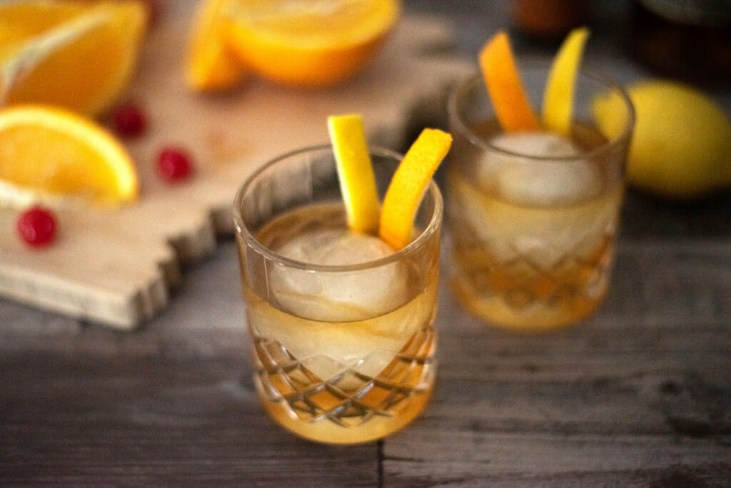 two drinks in etched short glasses with orange and lemons slices in them and oranges and cherries blurred in the background. Recipe for an Old Fashioned Cocktail