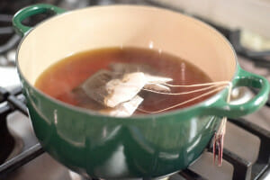 tea bags in a green pot on a stove. The perfect sweet tea recipe.