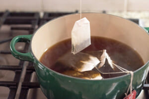 Putting a tea bag in a pot with bags steeping in steaming water.