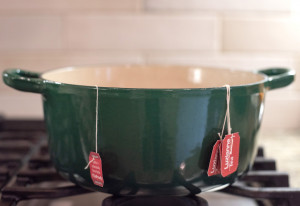 green pot sitting on a stove with strings of tea bags hanging over the edge.