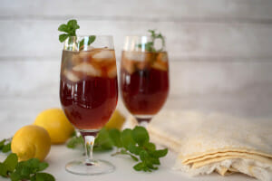 two cups of tea with ice and a mint leaf. The perfect southern sweet tea recipe.