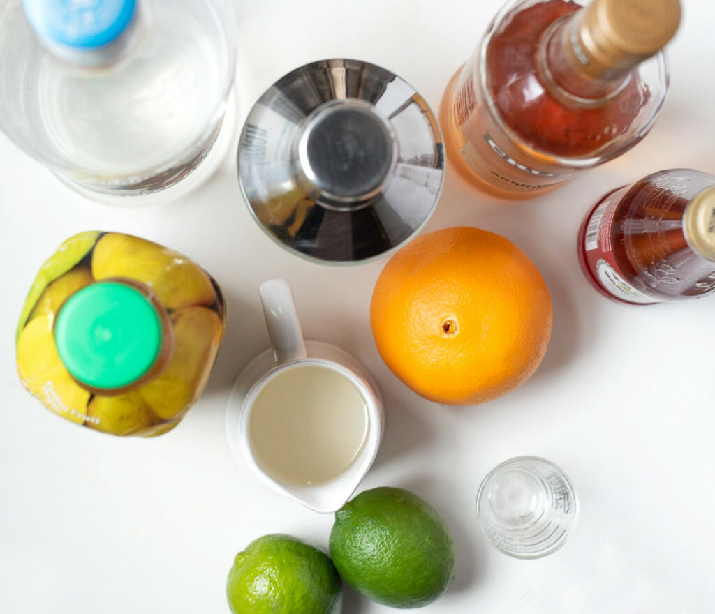 A grouping of ingredients to make a Hurricane cocktail. The photograph is shor from above and you can see some liquors, an orange, a couple of limes, a cocktail shaker, a shot glass, and a bottle of passion fruit puree.