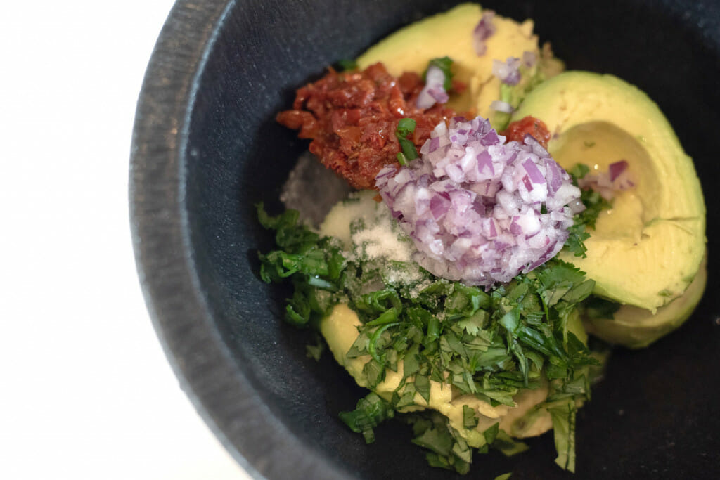 Ingredients for the Babalu guacamole recipe: sun-dried tomatoes, red onion, green onion, avocado, lime, cilantro, salt