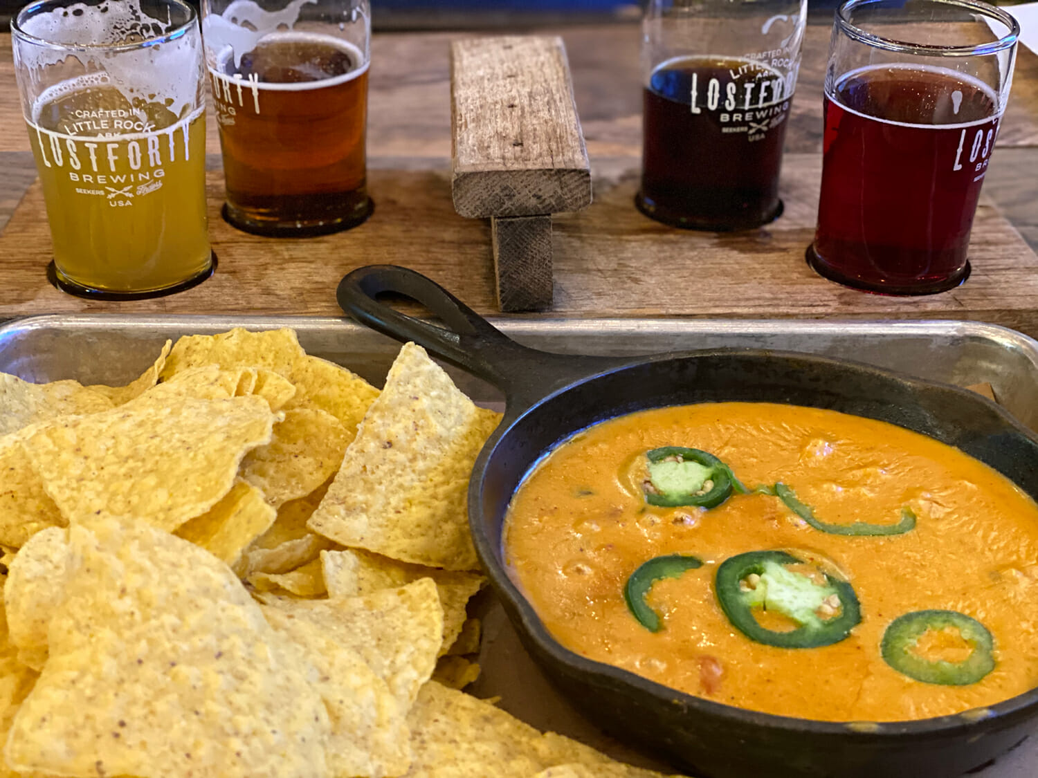 Cheese dip in an iron skillet with chips. There is beer in the background.