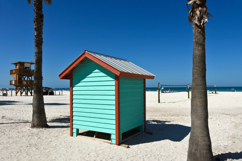 A small beach hut with volleyball nets behind it on manatee public beach on anna maria island.