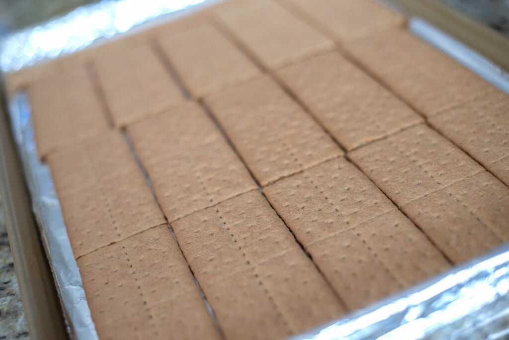 graham crackers spread out in a foiled lined edged cookie sheet. Ready to make graham cracker pralines.