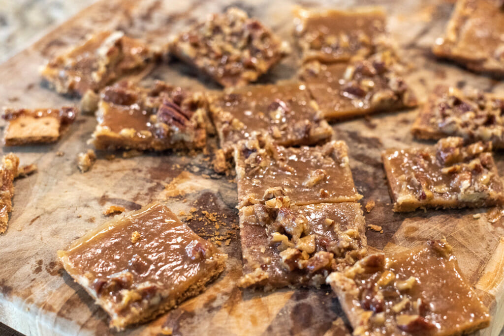 graham crackers with praline topping being cut on a cutting board.