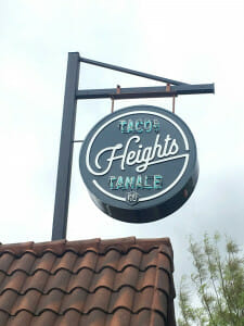 a sign against a gray sky that says Height's Tacos and Tamale