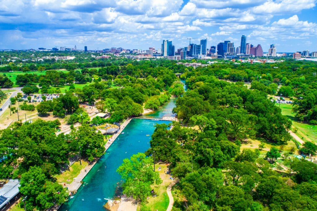 Aerial view of Barton Springs Pool in Zilker Park. You can see the city of Austin in the background.