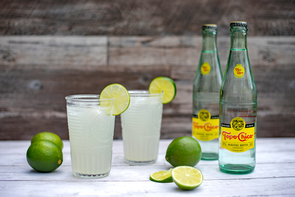 Photo of a drink called Texas Ranch Water. There are two glasses with a clear liquid garnished with a lime. Ther are limes on the counter and two bottles of a drink called Topo Chico