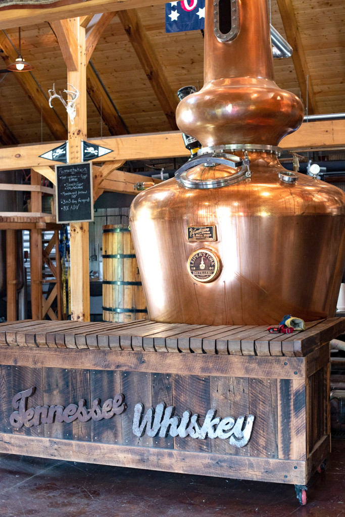 A sign that says Tennessee Whiskey with a copper distilling instrument on top.