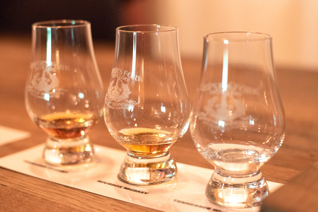 close up of three glasses with etching that says Leiper's Fork Distillery. There is a little bit of whiskey in each of the glasses from one that is very light to one that is amber colored.