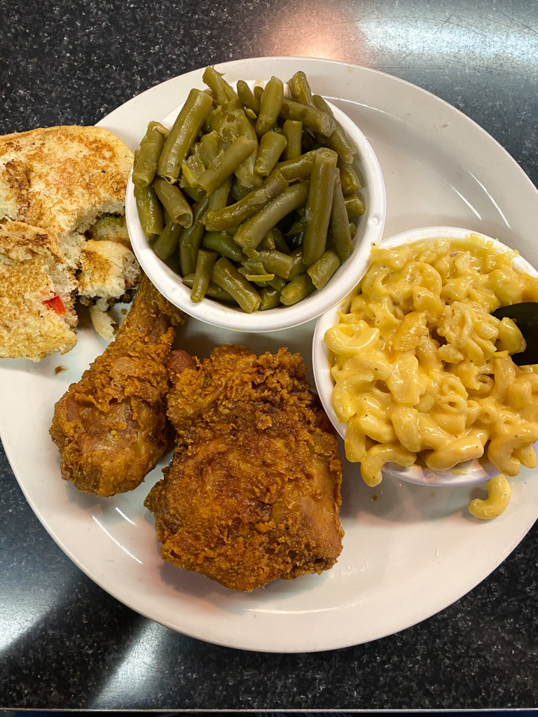 Food on a white plate and in two white bowls. There is fried chicken, green beans, and mac and cheese.