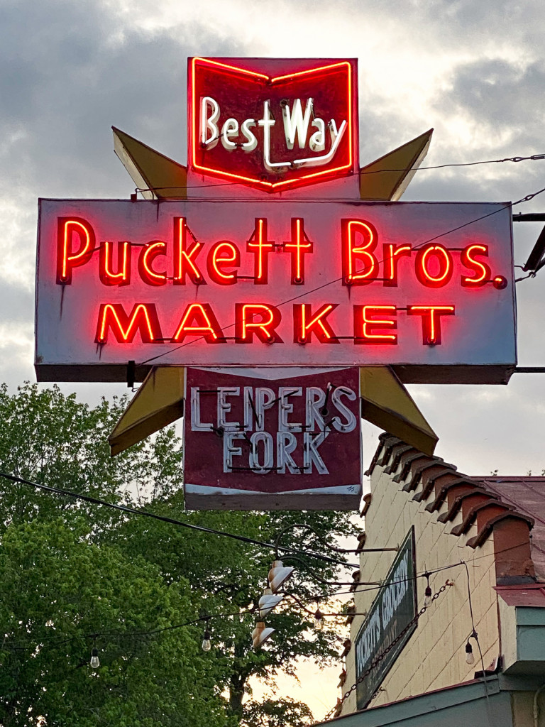 Close up of a neon sign that says Puckett Bros Market Leiper's Fork