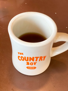 The Country boy, a restaurant in Leiper's Fork, Tn. There is a thick coffee mug with a small amount of coffee left in it.