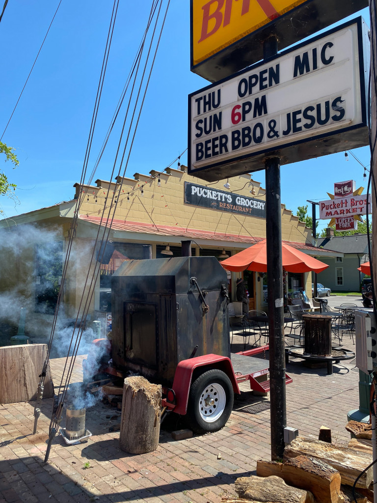 Puckett's Grocery in Leiper's Fork, Tn. Puckett's is a restaurant that has meat and three meals, barbecue and live music. The sign on the photo says sunday at 6pm Beer, BBQ, and Jesus. You can see smoke coming from the smoker.