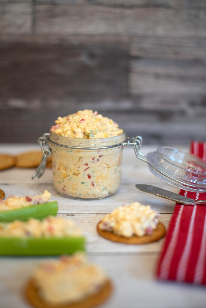 Southern Pimento cheese recipe. This photo shows a container of southern pimento cheese on celery and on crackers.