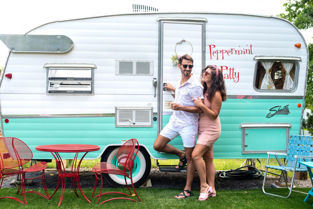 Couple outside of a vintage camper