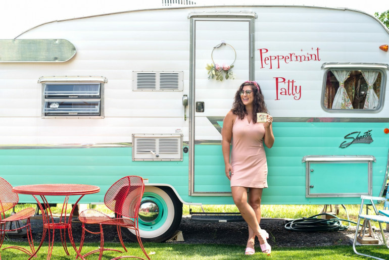 Young woman outside of a vintage camper