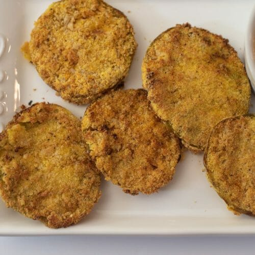 Photo of air fryer fried green tomatoes on a white plate on a white countertop. There is a remoulade sauce shown too.