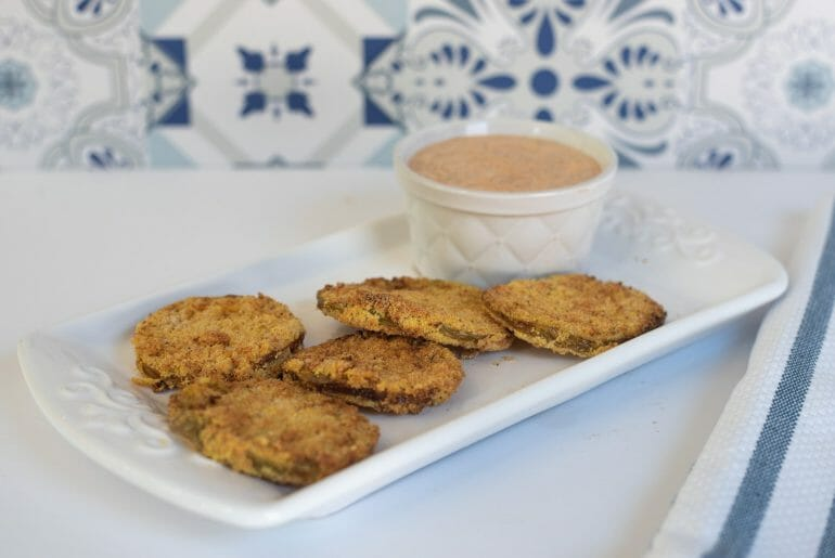 Photo of air fryer fried green tomatoes on a white plate on a white countertop. There is a remoulade sauce shown too. The background is blue and white tile.