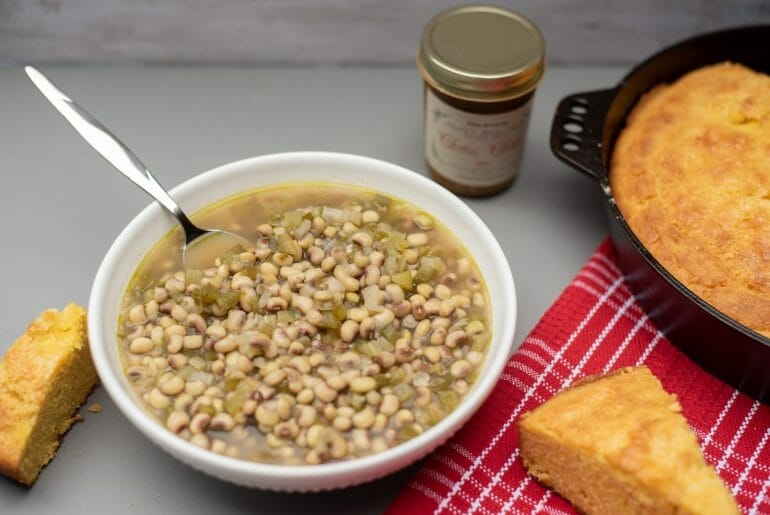 This is a photo of a bowl of purple hill peas with an iron skillet with cornbread in it. Purple hull peas are a perfect southern summer recipe. This is a vegetarian purple hull pea recipe.