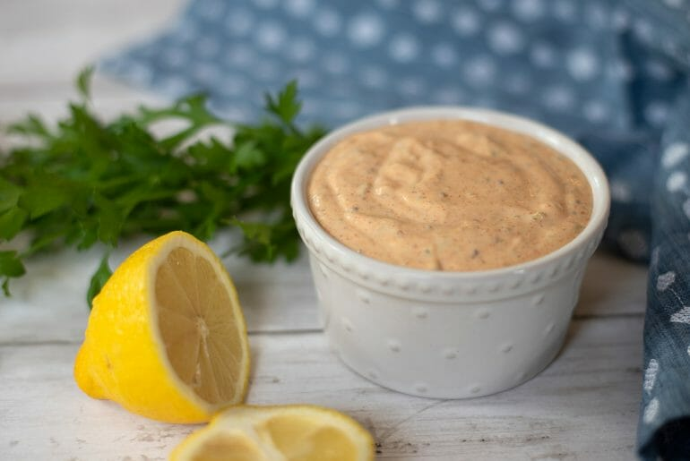 a small white ceramic bowl filled with Louisiana remoulade sauce. There is a blue dishtowel and some green parsley in the background and some lemons in the foreground.